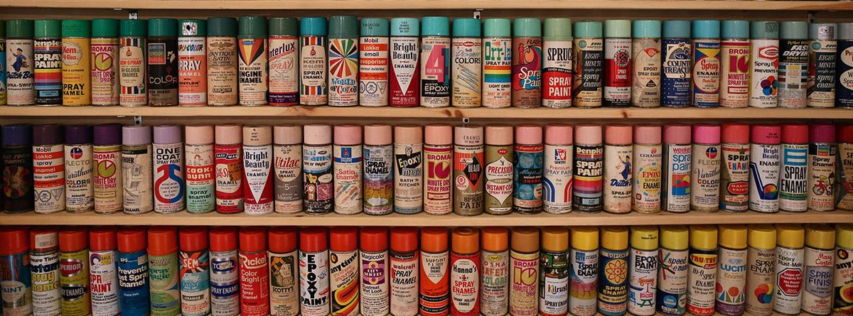 a shelving unit with hundreds of cans of spraypaint